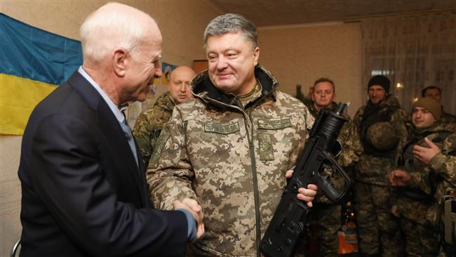 A handout photo released by the Ukrainian presidential press service shows Ukrainian President Petro Poroshenko (R) presenting the Ukrainian award weapon to US Senator John McCain (L) during their working trip to the Donetsk region in Shyrokine village on December 31, 2016.