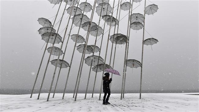 A woman holding an umbrella walks under an artistic sculpture during heavy snowfall in Thessaloniki, Greece, January 10, 2017. (Photo by AFP)