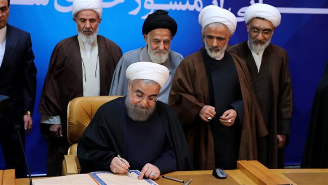 A handout picture provided by the office of Iranian President Hassan Rouhani on December 19, 2016 shows him signing documents as part of the landmark bill of rights that he unveiled, during a televised ceremony in Tehran. (Via AFP)