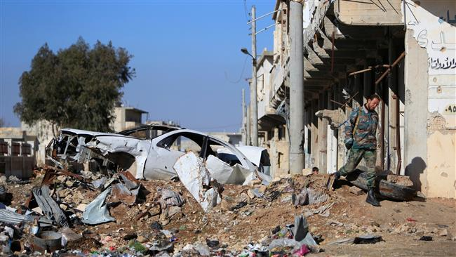 A Syrian government soldier walks near a damaged car on a road to Aleppo, Syria, on January 29, 2017. (Photo by Reuters)