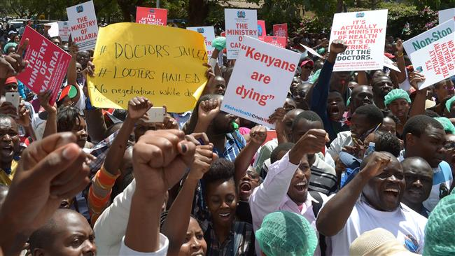 Striking doctors hold placards and chant slogans outside the Court of Appeal in Nairobi as they pushed for the release of jailed officials of the national doctors' union as they demanded fulfilment of a 2013 agreement between their union and the government that would raise their pay and improve working conditions on February 15, 2017. (Photo by AFP)