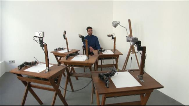 A model sits in front of the robots, which draw their face from different angles, creating five different portraits using cameras and facial recognition technology.