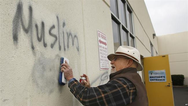 "A man paints over racist graffiti, which included such pronouncements as ""Muslims out,"" on the side of a mosque in what officials are calling an apparent hate crime, Roseville, California, Feb. 1, 2017. (Photo by AP)"