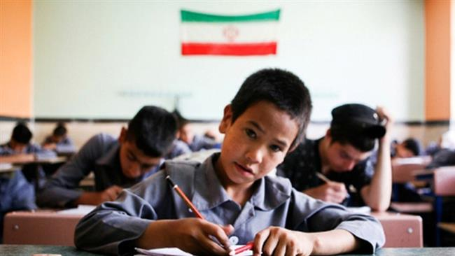 The file photo shows refugee children at a classroom in Iran.