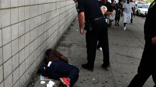 A police officer checks on a man who has passed out due to drug overdose in New York. (file photo)