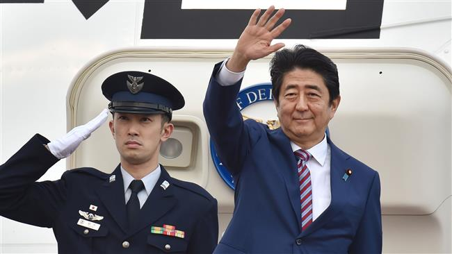 Japanese Prime Minister Shinzo Abe (R) waves before leaving Tokyo's Haneda Airport on March 19, 2017 for a four-day trip to Europe. (Photo by AFP)