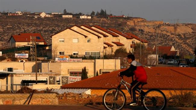 A boy rides his bicycle past houses in the Israeli settlements of Ofra, in the occupied West Bank February 6, 2017. © Reuters