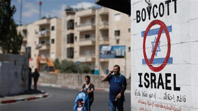 Palestinians walk past a sign painted on a wall in the West Bank town of Bethlehem on June 5, 2015, calling to boycott Israeli products coming from Jewish settlements. (AFP)