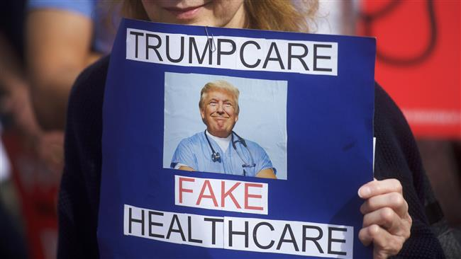 "A demonstrator holds a sign reading ""Trumpcare - Fake Healthcare"" during a health care rally at Thomas Paine Plaza on February 25, 2017 in Philadelphia, Pennsylvania. (Photo by AFP)"