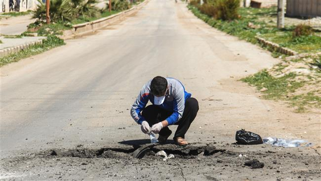 A Syrian man collects samples from the site of a suspected toxic gas attack in Khan Shaykhun, in Syria's northwestern Idlib province, on April 5, 2017. A US expert insists the inadequate clothing of the men inspecting the alleged attack proves that there could not have been a poisonous gas attack. (Photo by AFP)