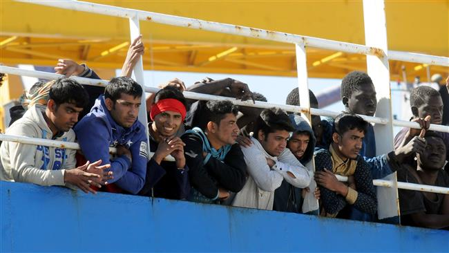 "Men wait on the deck of merchant ship ""Tuna 1"", at their arrival along with 470 refugees in the port of Palermo after being rescued at sea off the Libyan coasts, on April 18, 2017.  (Photo by AFP)"