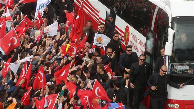 Turkish president Recep Tayyip Erdogan salutes supporters from a bus during a parade in Ankara, on April 17, 2017 following the results in a nationwide referendum. (Photo by AFP)