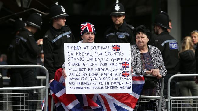 A man, wearing a Union flag themed had and draped in a Union flag, holds a placard as he waits to pay tribute outside of Southwark Cathedral in London on April 10, 2017, ahead of the funeral of PC Keith Palmer, the officer killed in the March 22 Westminster terror attack. (AFP)