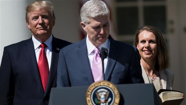 Neil Gorsuch (C) pauses while speaking after taking the judicial oath as US President Donald Trump (L) and Louise Gorsuch watch during a ceremony in the Rose Garden of the White House April 10, 2017 in Washington, DC. (Photo by AFP)