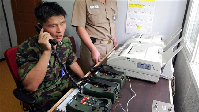 This file photo, taken on August 10, 2005, shows a South Korean lieutenant communicating with a North Korean officer during a phone call at a military office near the Demilitarized Zone (DMZ), in Paju, north of Seoul, as the two countries tested a hotline aimed at helping avoid naval confrontations in the Yellow Sea. (By AFP)