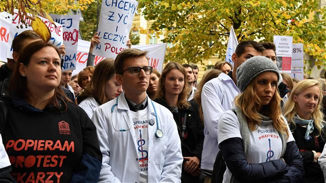 The photo taken on October 14, 2017 shows young doctors, medical students and supporters demonstrating in front of the government building in Warsaw, Poland, to demand better working conditions. (Photo by AFP)