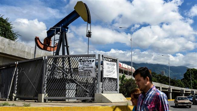 People walk by a small square with an oil pump in one of the access roads to the Central University of Venezuela, in Caracas on November 14, 2017. (Photo by AFP)