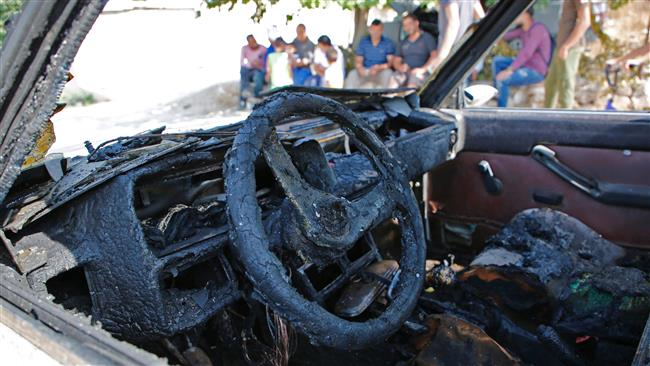 Palestinians from the village of Umm Safa, west of Ramallah in the occupied West Bank, seen in the background, check a vehicle, which was set ablaze on August 9, 2017 in an apparent arson attack by Israeli settlers. (Photo by AFP)