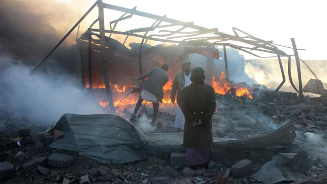 Smoke rises as Yemenis inspect the damage at the site of air strikes in the northwestern Huthi-held city of Sa'ada. (AFP)