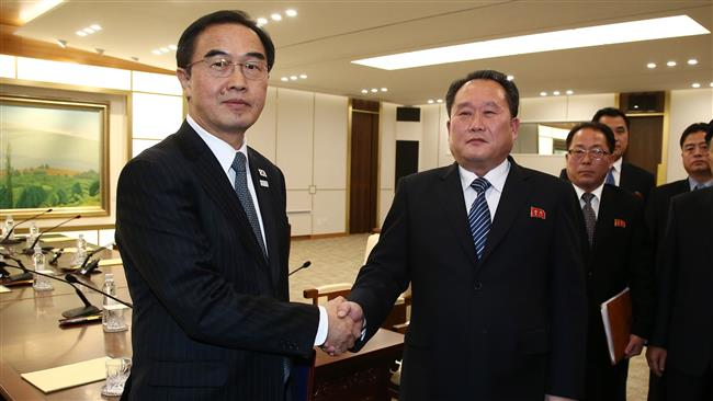 South Korea's Unification Minister Cho Myung-gyun (L) shakes hands with North Korean chief delegate Ri Son-gwon after their meeting at the border truce village of Panmunjom in the Demilitarized Zone (DMZ) dividing the two Koreas, January 9, 2018. (Photo by AFP)