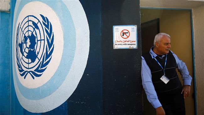 A Palestinian United Nations employee stands guard at the entrance of the UNRWA headquarters in Gaza City on January 8, 2018. (AFP)