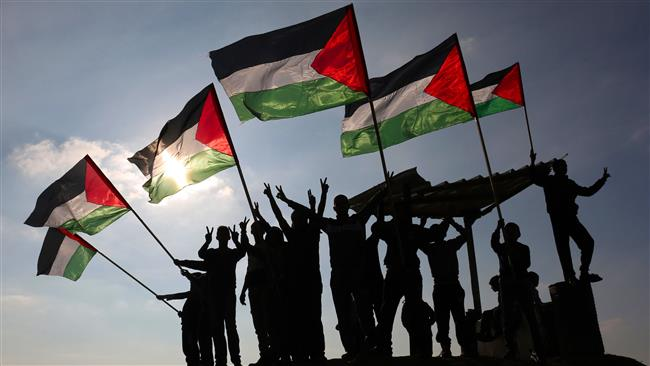 Palestinian protesters wave their national flag near the Israel-Gaza border east of the southern Gaza Strip city of Khan Yunis as they demonstrate against calls for the closure of UNRWA by the Israeli prime minister and cuts in Palestinian aid by the American president on January 9, 2018. (AFP)