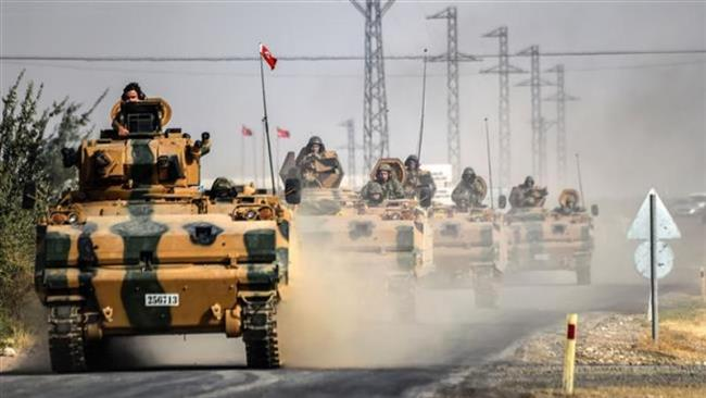 Photo taken around five kilometers (3.1 miles) west of the Turkish Syrian border city of Karkamis on August 25, 2016 shows Turkish army tanks driving to the Syrian Turkish border town of Jarabulus. (Photo by AFP)