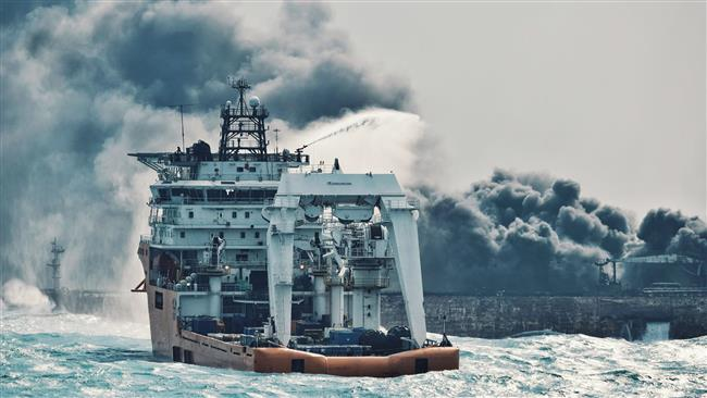"""This handout picture taken on January 10 and released on January 11, 2018 by Transport Ministry of China shows a Chinese offshore supply ship """"Shen Qian Hao"""" spraying foam on the burning oil tanker """"Sanchi"""" at sea off the coast of eastern China. (AFP)"""
