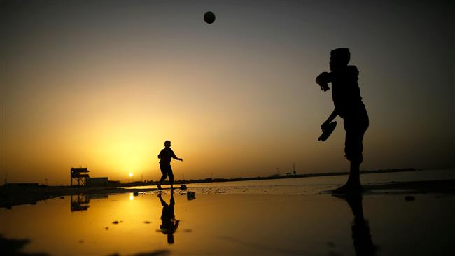 Palestinian boys play at the beach as the sun sets in Gaza City on January 11, 2018. (Photo by AFP)
