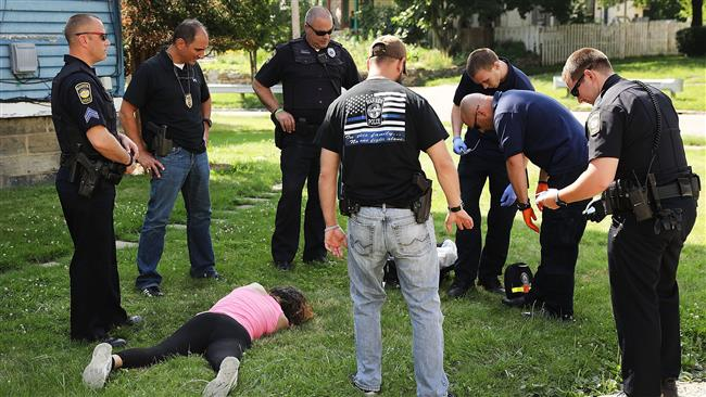 Medical workers and police treat a woman who has overdosed on heroin, the second case in a matter of minutes, on July 14, 2017 in Warren, Ohio. (Photo by AFP)
