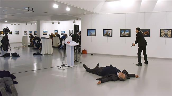 This photo taken on December 19, 2016, shows Andrey Karlov, the then Russian ambassador to Ankara, lying on the floor after being shot by Mevlut Mert Altintas (R) in an attack during a public event in Ankara, Turkey. (Photo by AFP)