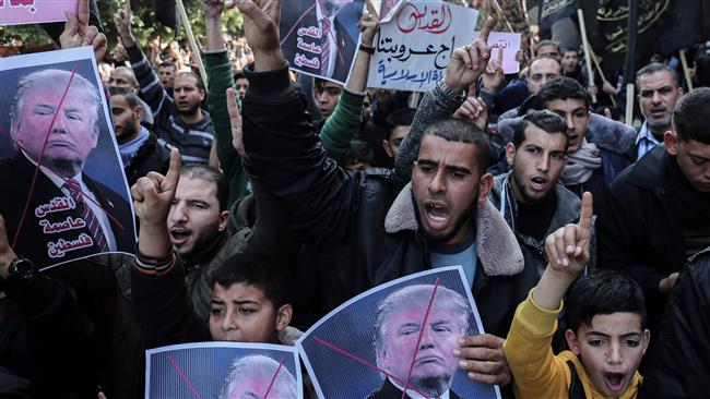 Palestinian supporters shout slogans and hold up portraits of US President Donald Trump during a protest against Trumps's decision to recognize Jerusalem as the capital of Israel, in the town of Rafah in the southern Gaza Strip, on January 12, 2018. (AFP)