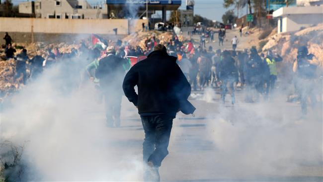 Palestinians run for covers from smoke-grenades during clashes with Israeli security forces following a demonstration in support of Palestinian prisoners on January 13, 2018, in the West Bank village of Nabi Saleh. (Photo by AFP)