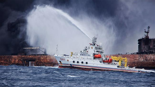 "This handout picture, taken and released on January 12, 2018 by the Transport Ministry of China, shows the Chinese firefighting vessel ""Donghaijiu 117"" spraying foam on the burning oil tanker ""Shanchi"" at sea off the coast of eastern China. (Via AFP)"