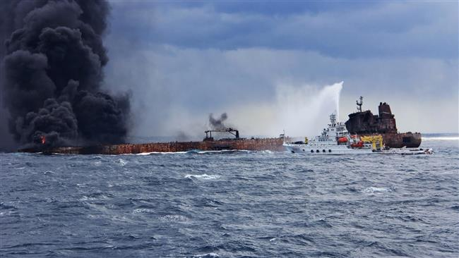 """This handout picture taken and released on January 12, 2018 by the Transport Ministry of China shows the Chinese firefighting vessel """"Donghaijiu 117"""" spraying foam on the burning oil tanker """"Sanchi"""" at sea off the coast of eastern China. (Via AFP)"""