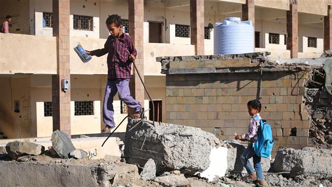 This file photo taken on March 16, 2017 shows Yemeni school children walking outside a school, that was damaged in  Saudi air strike in the southern Yemeni city of Ta'izz. (By AFP)