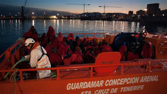 A group of migrants arrive on board a Spanish coast guard vessel, the second one of the day, at the southern Spanish port of Malaga, on January 13, 2018, following the rescue of an inflatable boat off the Spanish coast. (Photo by AFP)
