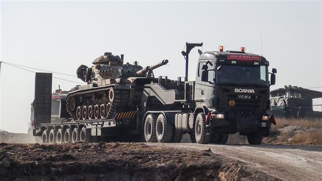 A photo made available by the Dogan News Agency shows Turkish army military trucks transporting armored vehicles to reinforce the border units in Sanliurfa close to the Syrian border on January 16, 2018. (Via AFP)