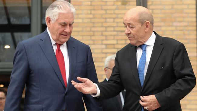 French Foreign Minister Jean-Yves Le Drian (R) gestures to US Secretary of State Rex Tillerson as they arrive for a group photograph during a meeting of diplomats on chemical attacks in Syria, in Paris on January 23, 2018. (Photo by AFP)