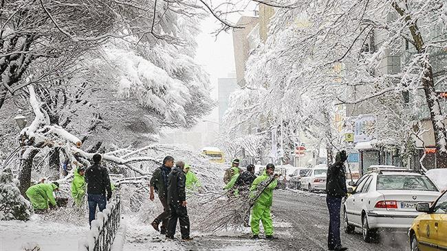 Municipality workers remove broken limbs from a street in northern Tehran, Jan. 28, 2018. (Photo by Tasnim)